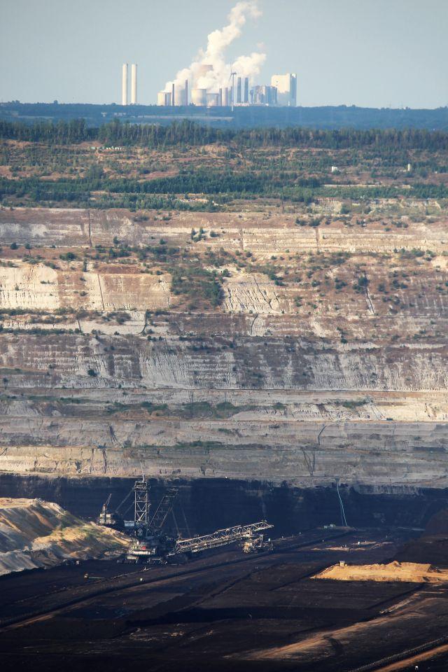 Über der dunklen Kohleschicht mit Schaufelradbagger erhebt sich die Kante des Tagebaus, und ganz oben steht ein qualmendes Kraftwerk.