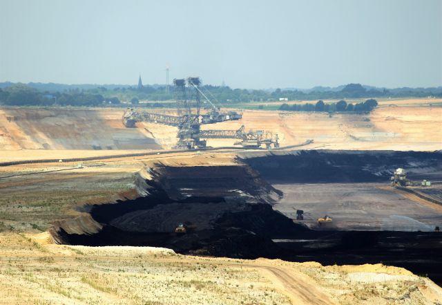 Blick in den Tagebau Garzweiler im Rheinischen Braunkohlerevier. Schaufelradbagger sind im Einsatz, die dunkle Kohleschicht zeichnet sich deutlich ab.