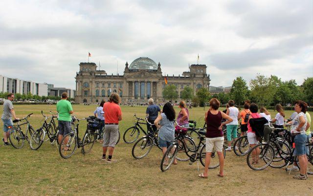 Im Hintergrund der Reichstag in Berlin, der Sitz des Deutschen Bundestags. Im Vordergrund auf der leicht bräunlichen Wiese eine Gruppe Radfahrer.