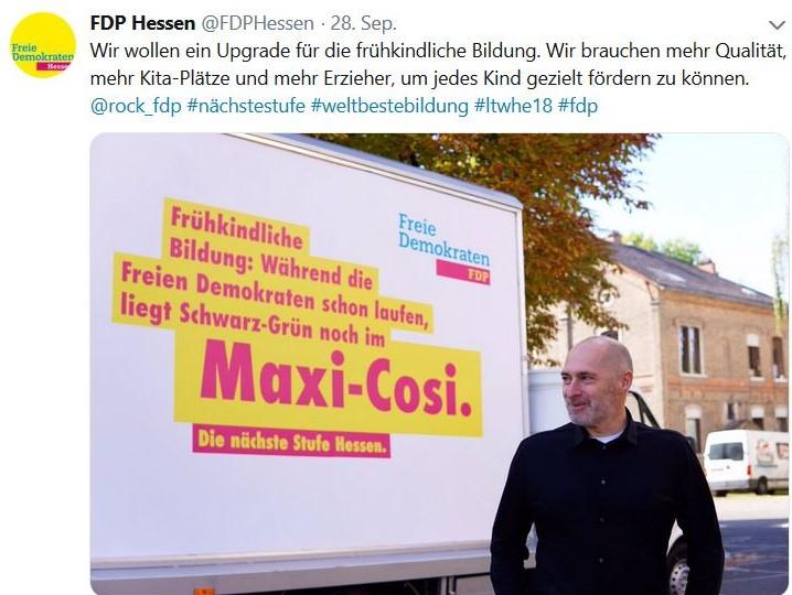 """René Rock vor einem fahrbaren Plakat mit dem Text """"Während die Freien Demokraten schon laufen, liegt Schwarz-Grün noch im Maxi-Cosi"""""""