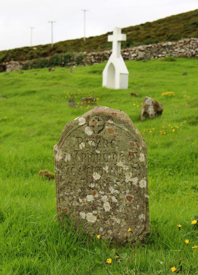 Ein Grabstein mit irischer Aufschrift auf grünem Gras. Im Hintergrund ein weißes Kreuz.