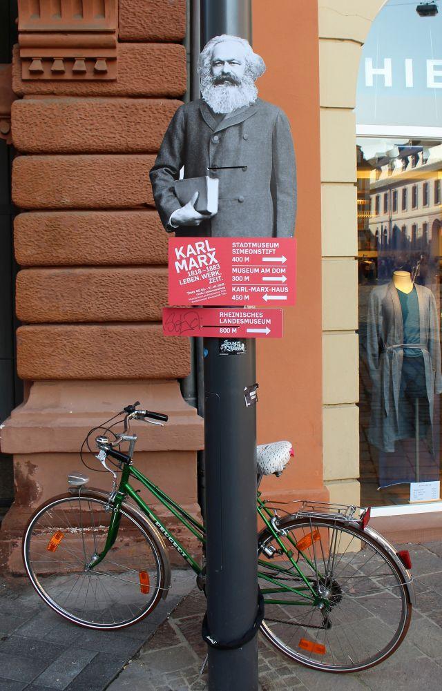 Karl Marx mit Hinweisschildern zu den einzelnen Austellungn als Plakat an einem Lichtmasten. Unten steht ein Farrad.
