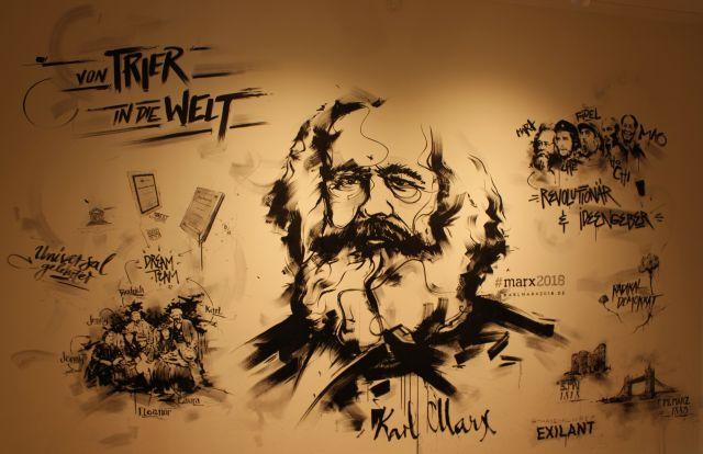Karl Marx in der Mitte der Wand als Zeichnung und um ihn herum seine 'Jünger', die mit mehr oder weniger demokratischen Mitteln für den Marxismus kämpften.