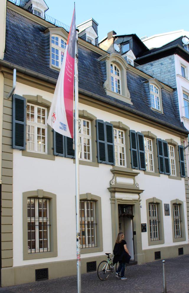 Geburtshaus von Karl Marx. Links ein Fahnenmast mit Hinweisbanner für die Ausstellung.