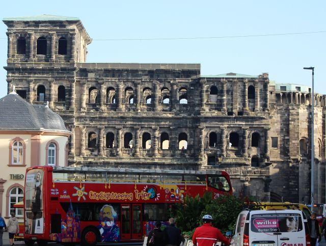 Roter Sightseeing-Bus mit demBild von Karl Marx vor der Porta Nigra in Trier. Die Porta Nigra ist ein wehrhaftes Stadttor aus römischer Zeit.