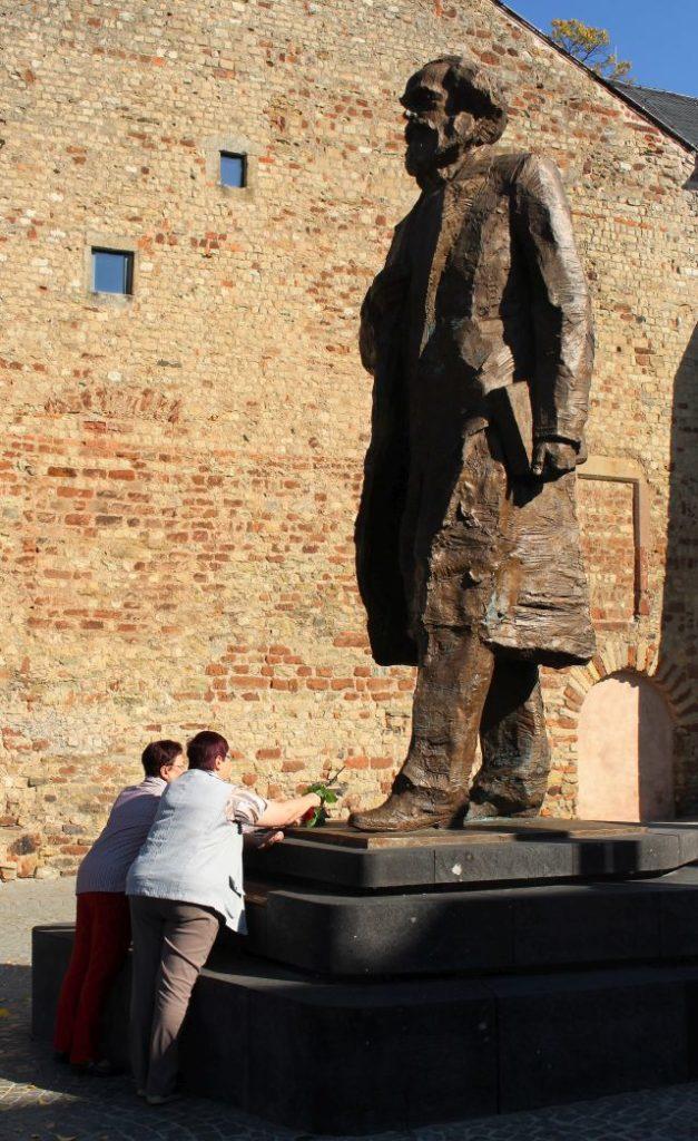 Zwei Frauen legen Rosen nieder. Über ihnen erhebt sich Karl Marx in Bronze. Er trägt einen Gehrock und hält ein Buch unter dem Arm. Im Hintergrund eine Backsteinmauer.