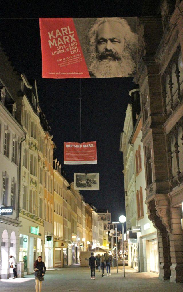 Banner mit Karl Marx über der nächtlichen Fußgängerzone. Danach weitere Banner mit Menschen, die denNamen Marx tragen.