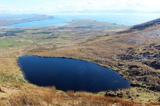 In kräftigem Blau hebt sich der Mount Eagle Lake vom winterlichen Bewchs ab. Im Hintergrund die Dingle Bay.