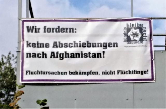 """Banner an einer hellen Hauswand mit der Aufschrift """"Wir fordern: Keine Abschiebungen nach Afghanistan. Fluchtursachen bekämpfen, nicht Flücvhtlinge!"""""""