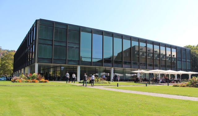 Der in dunklen Tönen gehaltene Landtag in Stuttgart mit einer breiten Glasfront. Davor der Außenbereich des Restaurants.
