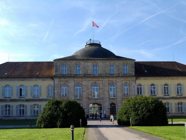 Das Hauptgebäude der Universität Hohenheim. Heller Putz und dunkles Dach.