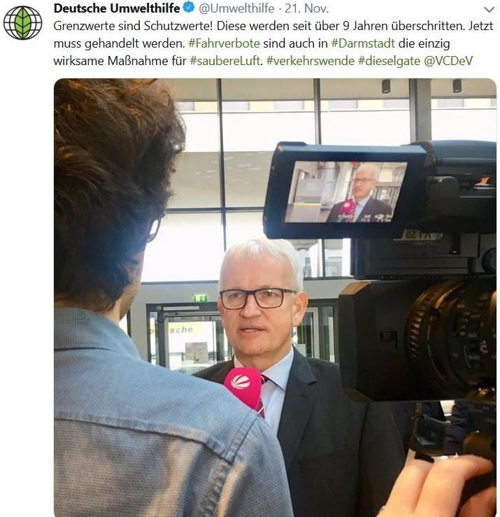 Jürgen Resch mit einem roten Mikrophon und rechts einer Fernsehkamera.