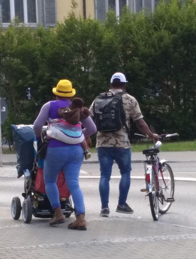 Migrantenfamilien von hinten in bunter Bekleidung mit Kinderwagen und Fahrrad.