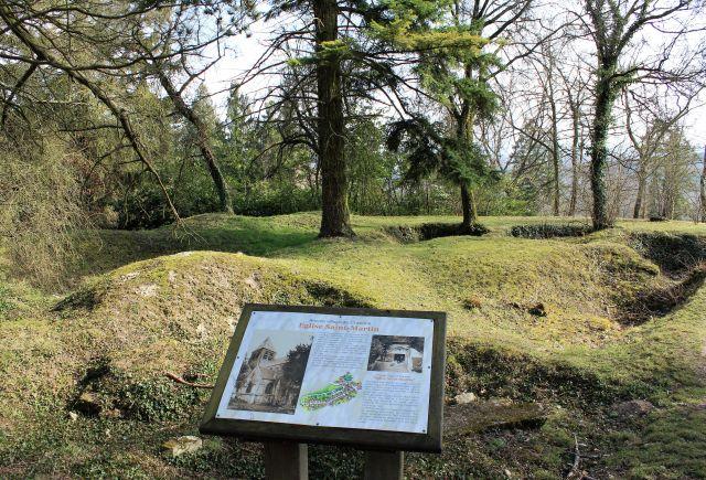 Im Vordergrund eine kleine Informationstefel zur zerstörten KIrche des Ortes Craonne, dahinter die längst überwachsenen Keller der Gebäude sowie hochgewachsene Bäume.