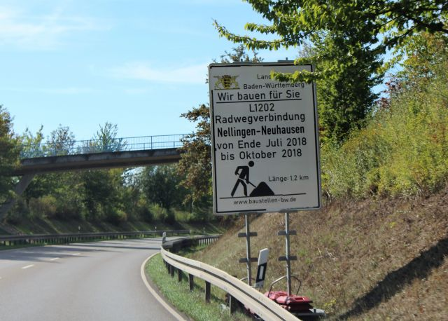 Eine Brücke über eine Landstraße wird zu Lasten der Fahrbahnen für Autos um einen Radweg ergänzt.