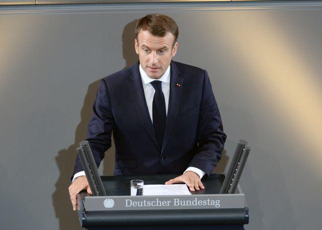 Macron mit Anzug und Krawatte am Rednerpult im Reichtag.