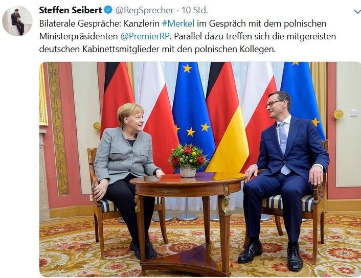 Angela Merkel mit gruem Blazer und Mateusz Morawiecki im dunkleblauen Anzug an einem runden Holztisch. Auf diesem stehen Blumen, im Hintergrund die polnische und deutsche sowie die EU-Fahne.