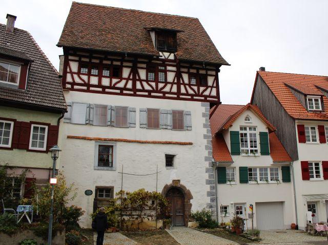 Fachwerkgebäude mit weißem Putz im unteren Bereich und sichtbaren braunen Balken im oberen Stockwerk.