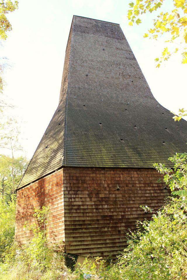 Die Fassade des Abluftkamins ist mit Holzschindeln gestaltet. Die Grundkonstruktion besteht aus Beton. Der Kamin ist von grünen Bäumen umgeben.