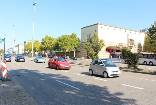 Autos in weiß und rot usw. fahren auf der B 14. Im Hintergrund das Haus der Geschichte Baden-Württemberg, ein modernes Gebäude.