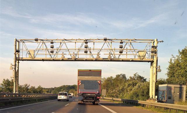 Mautbrücke mit verschiedenen Erfassungsgeräten an einem Metallrahmen über der Autobahn.