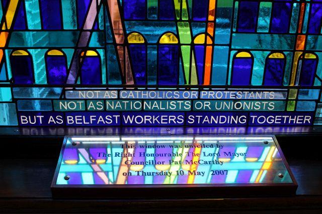 Farbiges modernes Glasfenster in der Belfaster City Hall mit der eingelegten Schrift: 'Not as catholics or protestants / not as nationalists oder unionists / But als Belfast workers standing together'.