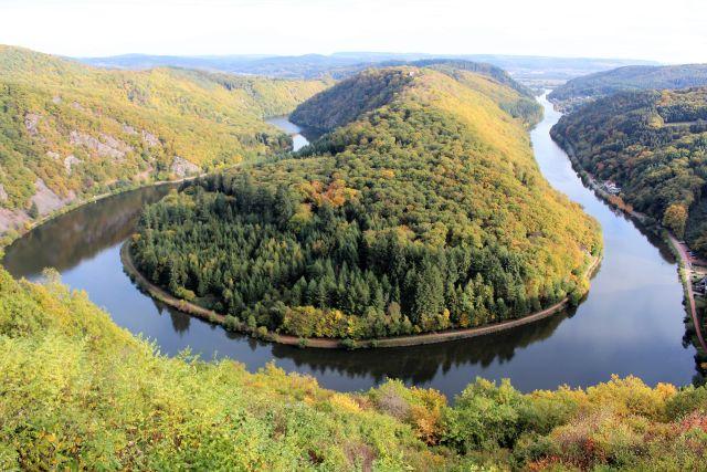 Der Fluss Saar zieht sich in einer Schleife zwischen bewaldeten Höhen hindurch.