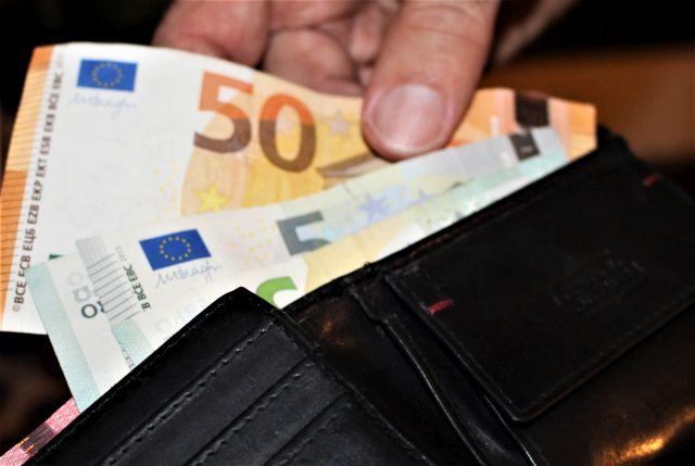 Eine Hand zieht einen 50 EURO-Schein aus einem schwarzen Geldbeutel und lässt die kleineren Scheine drin.