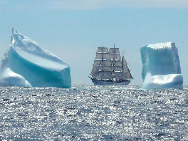 Die Gorch Fock zwischen zwei gleich hohen Eisbergen, die leicht bläulich schimmern.