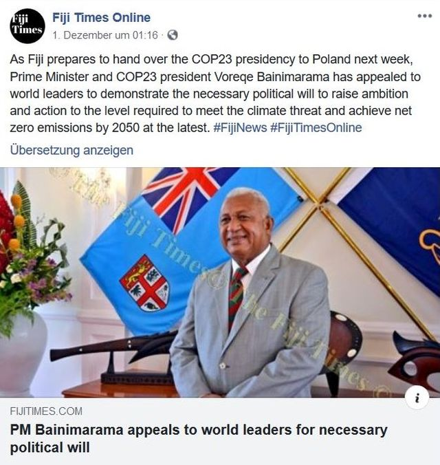 Der Präsident der Fiji-Inseln im grauen Anzug vor einer Flagge seines Staats.