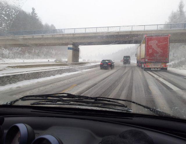 Roter Lkw auf einer schneebedeckten Autobahn kurz vor einer Brücke. Aufgenommen aus einem nachfolgenden Smart-Pkw.