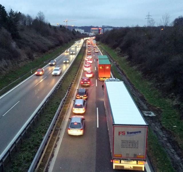 Fahrzeuge in Kolonne auf der Autobahn A 81 bei Sindelfingen. Die Lichter sind eingeschaltet, die Dämmerung hat eingesetzt.