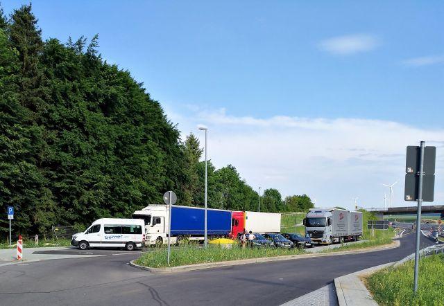 Pkw und Lkw drängeln sich auf einem zu kleinen Parkplatz. Die Lkw in blauer, weißer und roter Farbe. Davor ein weißer Sprinter-Transporter.