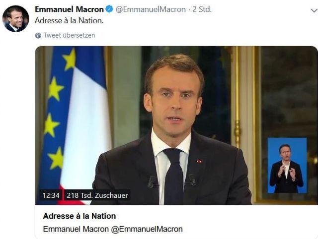 Macron mit Anzug und Krawatte vor der französischen und der EU-Flagge.
