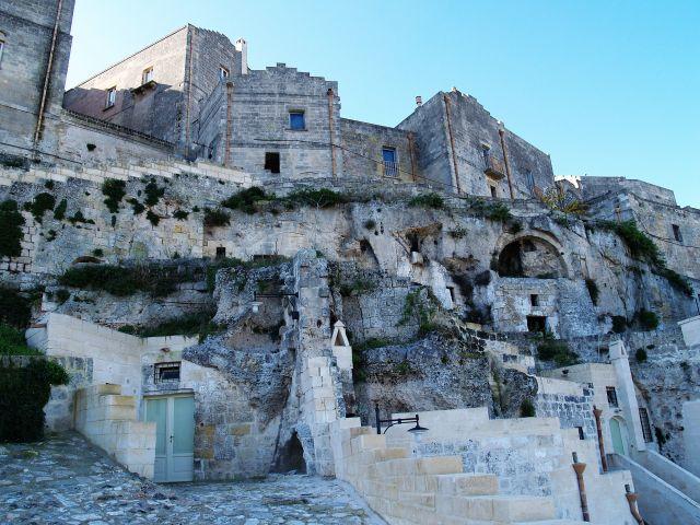 Im unteren Bereich Felsenwohnungen und darüber historische Steinhäuser.