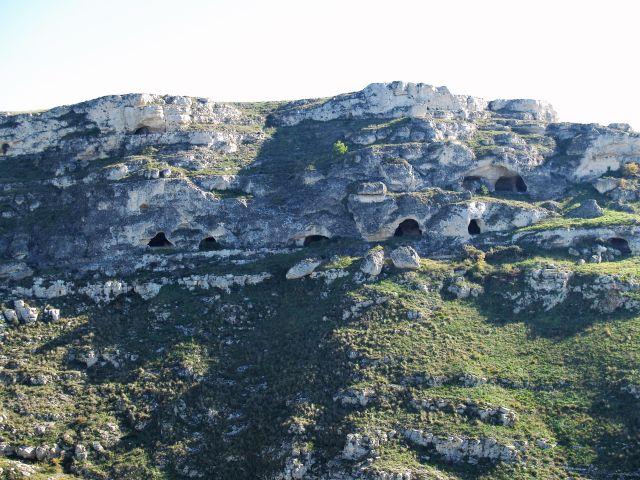 Natürliche Höhlen im Gestein, umgeben von leichtem grünen Bewuchs.