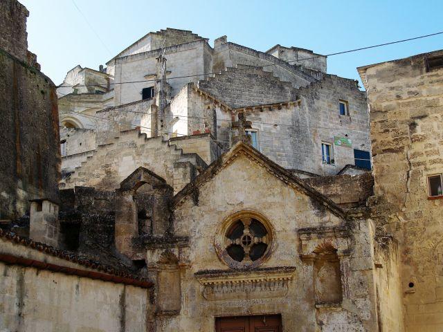 Blick auf eine in den Fels gebaute kleine Kirche aus hellem Stein. Ein rundes Fenster mit einem Kreuz ist zu sehen.