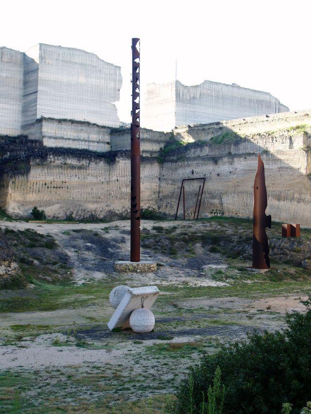 Netallskulpturen vor Wänden aus Tuffstein.