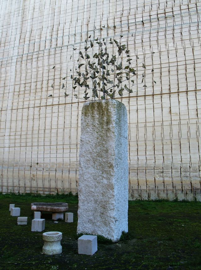 Auf einem hohen rechteckigen hellen Stein steht eine filigrane Skulptur aus feinen Metallblättchen.