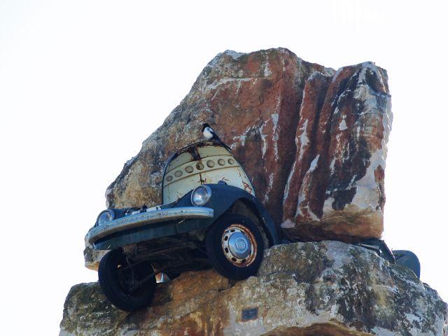 Ein Auto scheint zwischen Felsen eingequetscht zu sein. Nur der hintere Teil ragt heraus.