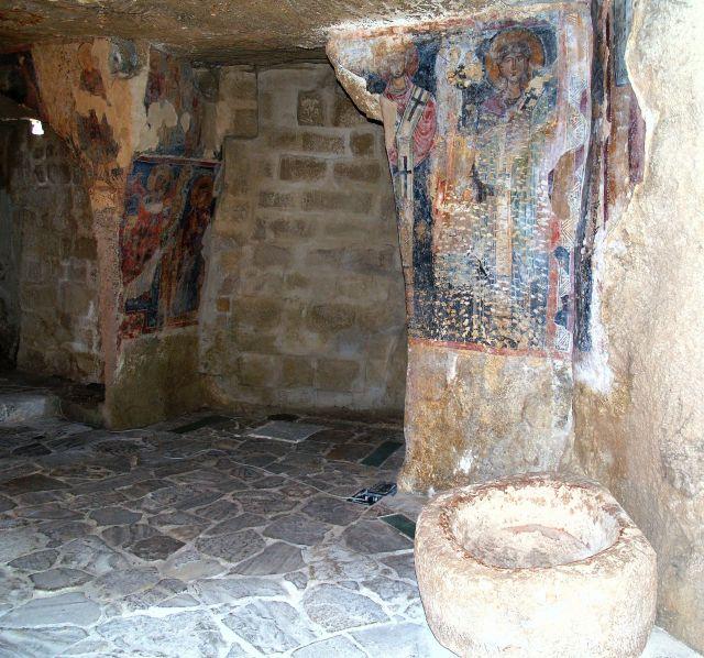 Rste der Wandmalerei in einer von Säulen getragenen Felsenkirche.