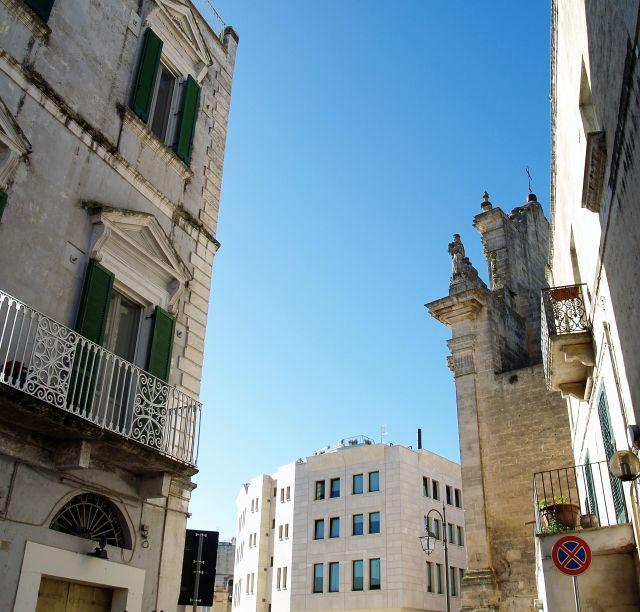 Historische Gebäude mit Balkonen und Rollos, dazwischen ein schlichter Neubau - alles in hellem Stein.
