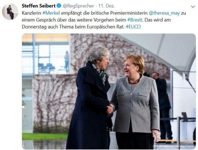 Theresa May im dunklen Mantel und Angela Merkel im hellen Blazer mit dunkler Hose. Sie schütteln sich die Hände.