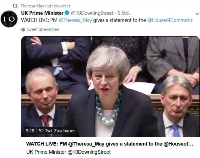 Theresa May mit dunklem Blazer und einer Kette mit großen Kugeln im Parlament am Rednerpult.