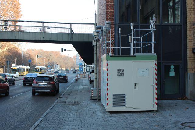 Die Messstation besteht aus einem grauen Container, an dem zahlreiche Messgeräte befestigt sind. Sie steht sehr nahe an der Fahrbahn, und zwei Mauern stehen so, dass auch das letzte Staubkörnchen dort landet.