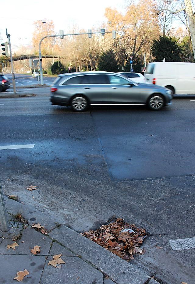 Blätter und andere Teile haben die Dohle verstopft. Im Hintergrund Fahrzeuge auf der Kreuzung am Neckartor in Stuttgart.