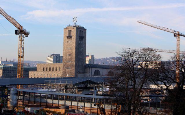Im Mittelpunkt der Bahnhofsturm, umgeben von gelben Kranen und einer umfassenden Baustelle.