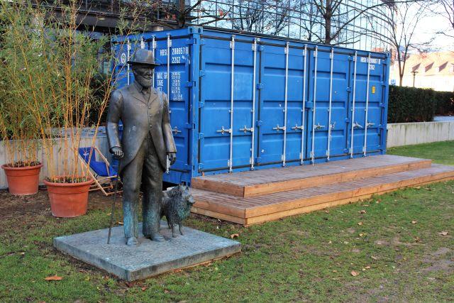Die Skulptur umfasst Wilhelm II. im Gehrock mit Hut und Stock sowie zwei kleine Hunde. Dieses Denkmal steht jetzt unmittelbar neben einem blauen Transportcontainer.