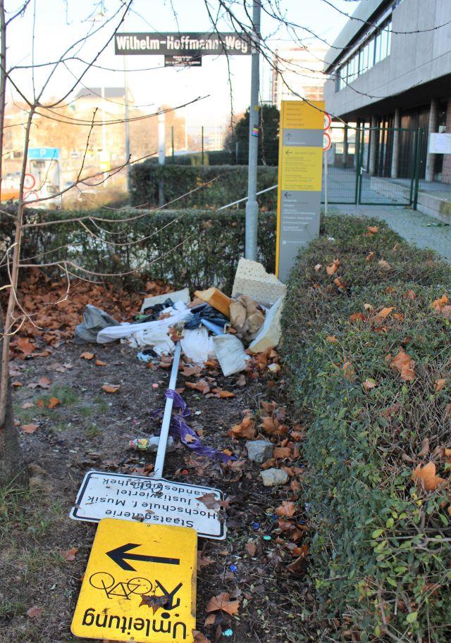 Ein umgestprzter Wegweisen, Mülltüten und große Teile von Unrat in einer Ecke.