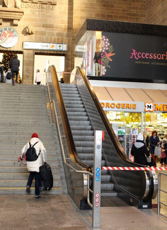 Eine Frau im hellen Mantel trägt ihren Koffer die Eingangstreppe zum Bahnhof hoch. Die Rolltreppe ist defekt und abgesperrt.